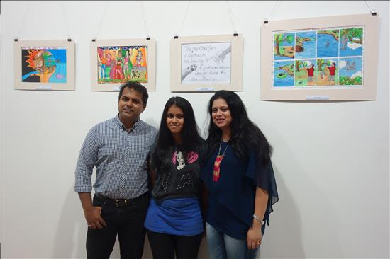 Yound artist flanked by parents with painting in the background