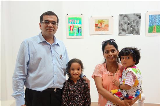 The girl standing with her painting in the background along with parents and younger sibling