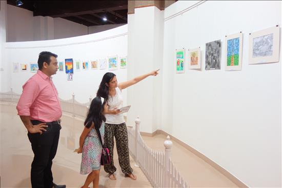 Parents keenly looking at the paintings on display