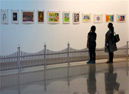 Participating child artist with parent looking at the display