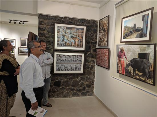 Cinematographer Dhananjay Kulkarni looks at the pictures along with Bageshree Ponkshe from Jnana Prabodhini at Indiaart Gallery