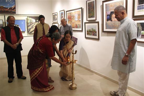 Dr. Swarnalata Bhishikar, Smt. Ganesh and Smt. Mangala Narlikar light the lamp at the inauguration of Milind Sathe's solo photography show at Indiaart Gallery