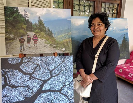 Jyoti Kanitkar with the picture of the kids going to school in the mountains at Indiaart Gallery