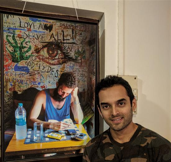 Saurabh Gokhale in front of the picture he picked up from Milind Sathe's photography show