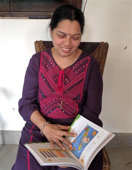Smt. Khadilkar, an art teacher browses through Khula Aasmaan catalog