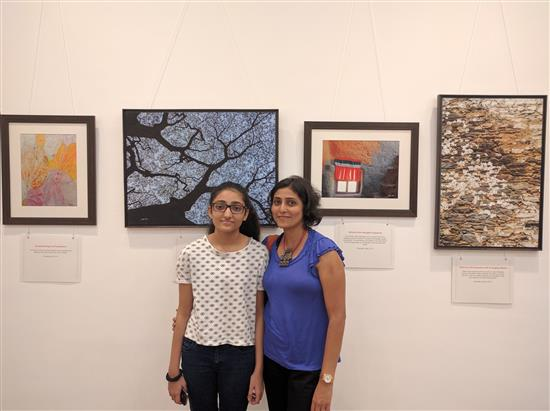 Artist Ami Patel with daughter Khushi in front of pictures from Milind Sathe's solo photography show at Nehru Centre, Worli, Mumbai (August 2016)