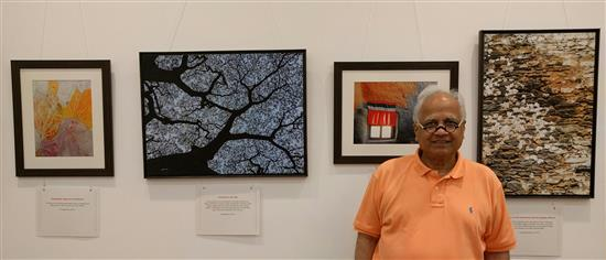 Sudhir Jambhekar in front of the pictures he liked at Milind Sathe's solo photography show at Nehru Centre, Worli, Mumbai - August 2016